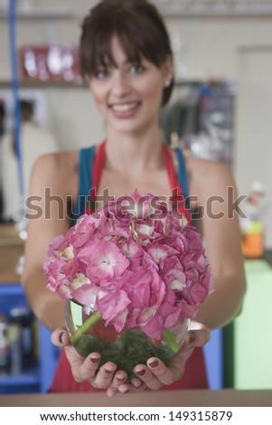 Portrait of female florist holding pink hydrangea in flower shop - stock photo