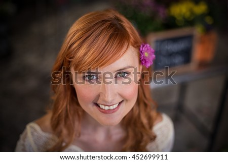 Portrait of female florist smiling in the flower shop - stock photo