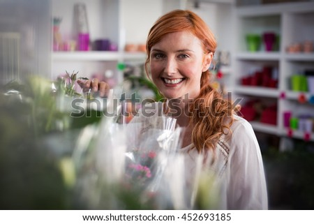 Portrait of female florist standing and smiling in the flower shop - stock photo