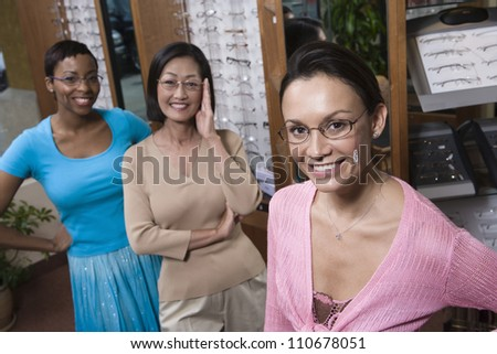 Portrait of female friends trying on glasses at optometrist
