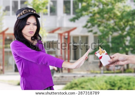 Portrait of female high school student refuse to smoke in the school - stock photo