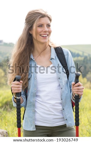 Portrait Of Female Hiker Holding Hiking Poles In Countryside - stock photo