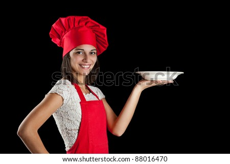 Portrait of female in chef uniform and chef hat showing plate - stock photo