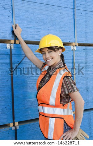 Portrait of female industrial worker standing by stacked wooden planks - stock photo