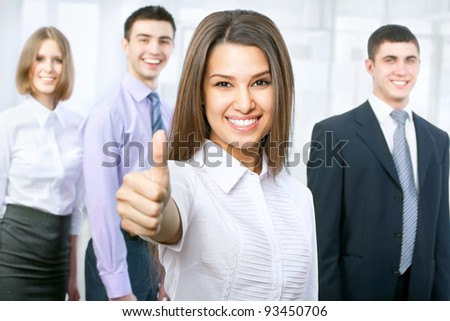Portrait of female leader showing thumb up with cheerful team in background - stock photo