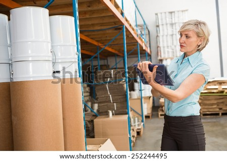 Portrait of female manager using digital tablet in warehouse - stock photo