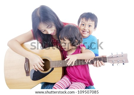 Portrait of female musician plays guitar with her children. shot in studio isolated on white - stock photo
