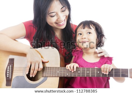 Portrait of female musician plays guitar with her daughter - stock photo