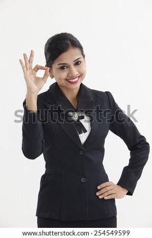 portrait of female okay gesturing, isolated on white - stock photo