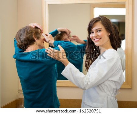 Portrait of female ophthalmologist assisting senior woman to insert contact lens in front of mirror - stock photo