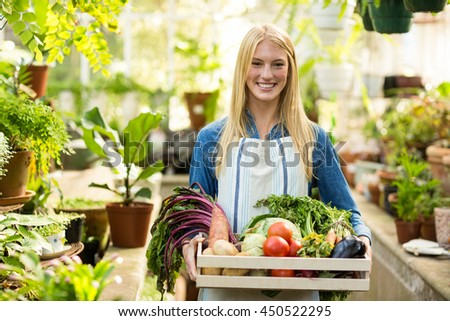 Portrait of female owner holding fresh vegetables in crate at greenhouse