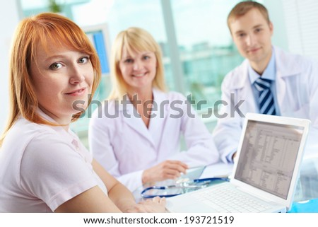 Portrait of female patient looking at camera on background of two practitioners - stock photo