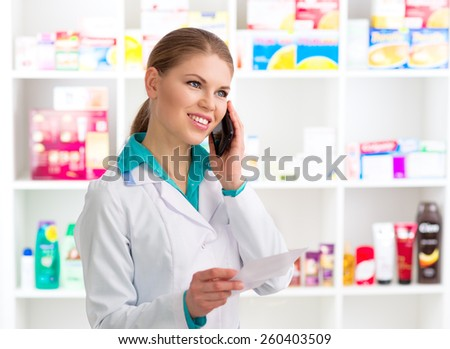 Portrait of female pharmacist consulting customer on phone holding recipe. Young woman medical assistant in pharmacy.  - stock photo
