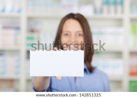 Portrait of female pharmacist holding blank placard in pharmacy - stock photo