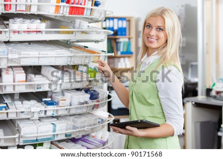 Portrait of female pharmacist holding tablet PC at pharmacy - stock photo