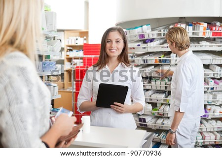 Portrait of female pharmacist holding tablet PC while attending customer on the counter - stock photo