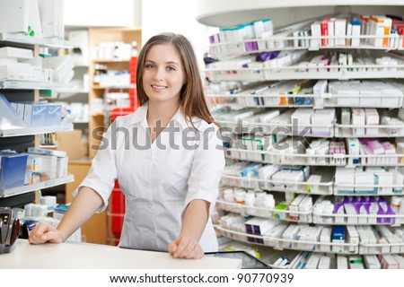 Portrait of female pharmacist standing at counter in pharmacy - stock photo