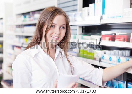 Portrait of female pharmacist working in pharmacy drugstore - stock photo