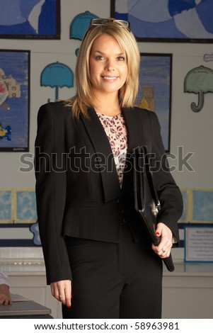 Portrait Of Female Primary School Teacher Standing In Classroom