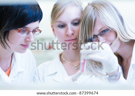 portrait of female researchers/chemistry student carrying out research in a chemistry lab (color toned image; shallow DOF) - stock photo