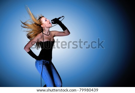 Portrait of female rock singer with microphone - stock photo