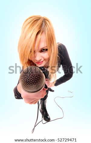 Portrait of female rock singer with microphone in hand over blue