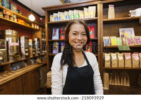 Portrait of female salesperson smiling in coffee shop - stock photo