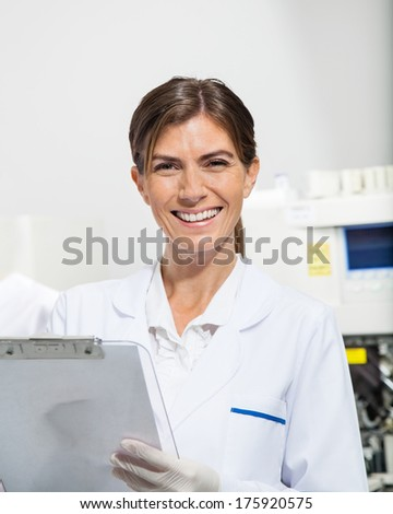 Portrait of female scientist holding clipboard in laboratory