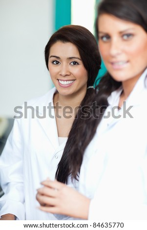 Portrait of female scientists posing with the camera focus on the background - stock photo