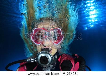 Portrait of female scuba diver underwater with bubbles  - stock photo