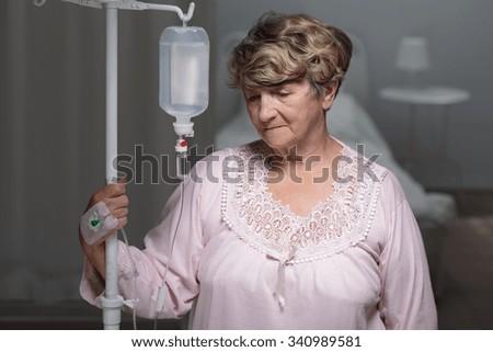 Portrait of female senior patient with drip - stock photo