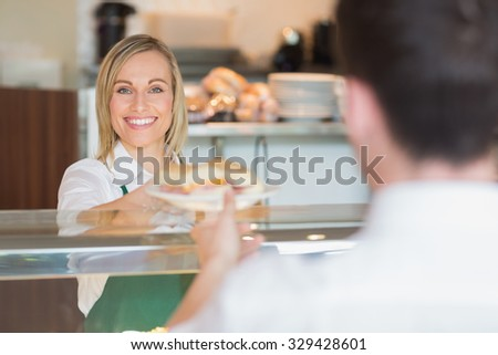 Portrait of female shop owner smiling while giving sandwich to customer in bakery - stock photo
