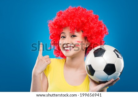 Portrait of female soccer fan showing the amount of goals with her finger - stock photo