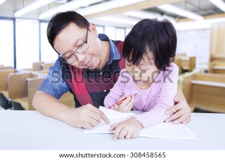 Portrait of female student studying with male teacher in the classroom and try to write - stock photo