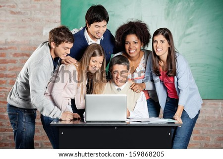 Portrait of female students standing with classmates while teacher teaching on laptop in classroom - stock photo