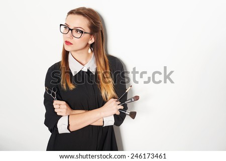 Portrait of female stylist standing with hairdresser's accessories and makeup brushes - stock photo