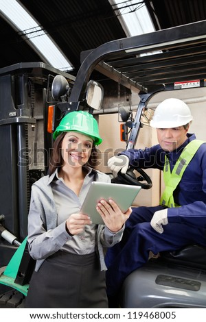 Portrait of female supervisor and forklift driver with digital tablet at warehouse - stock photo