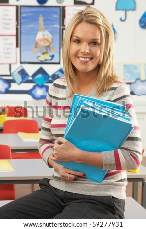 Portrait Of Female Teacher Sitting At Desk In Classroom - stock photo