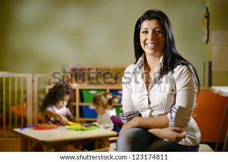 Portrait of female teacher smiling at camera and happy children eating lunch at school. Copy space - stock photo