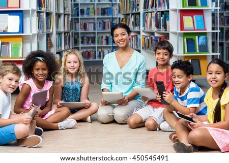 Portrait of female teacher with children holding digital tablets in library