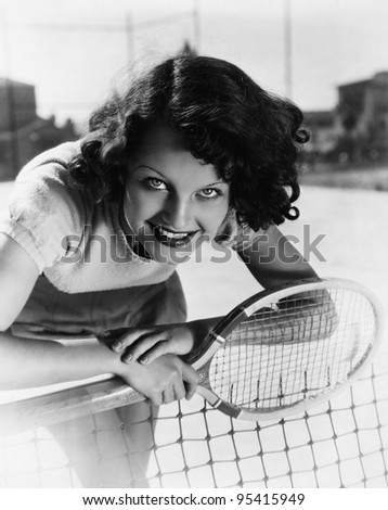 Portrait of female tennis player at the net - stock photo