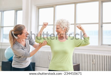 Portrait of female trainer looking at elderly woman flexing her bicep at the rehabilitation center. Happy about her recovery at rehab. - stock photo