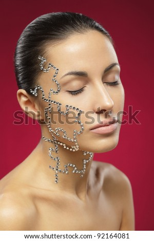 Portrait of female with beauty crystal puzzle on her face - stock photo