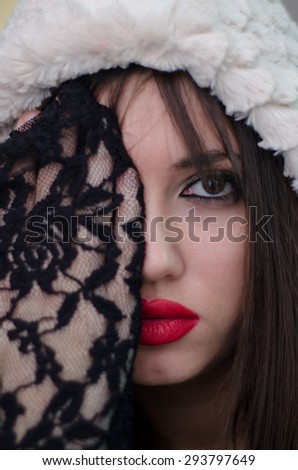 Portrait of female with cute face and bold red lips, wearing hood and lace gloves. Hide her eye with the palm