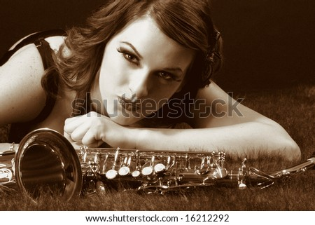 Portrait of female with saxophone in retro lingerie. Image stylized as old picture including adding some artificial GRAIN. - stock photo