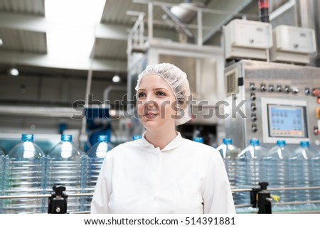 Portrait of female worker in protective working wear, standing in front of huge line for water bottling.