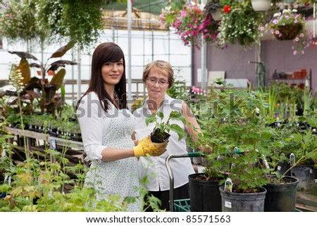 Portrait of female worker standing with customer - stock photo