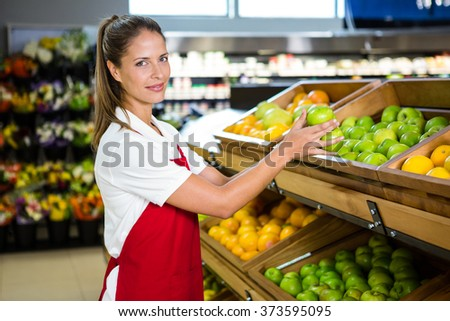 Portrait of female worker taking fruit in grocery store - stock photo
