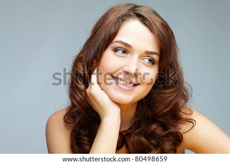 Portrait of feminine woman touching her face and looking aside