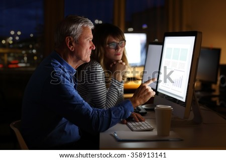 Portrait of financial analysts consulting and working on computers at late night at office. Senior businessman and professional woman sitting in front of monitors and analyzing financial data Teamwork - stock photo